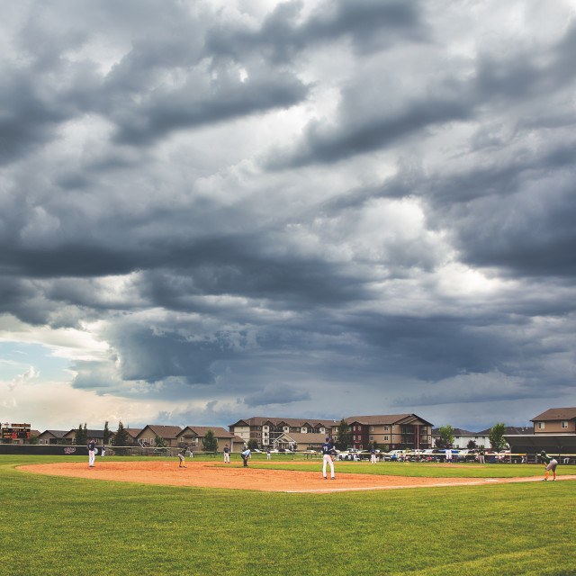 """""""Blue and gray storm clouds over a high school baseball game lined by apartment buildings in a stormy summer landscape"""" stock image"""