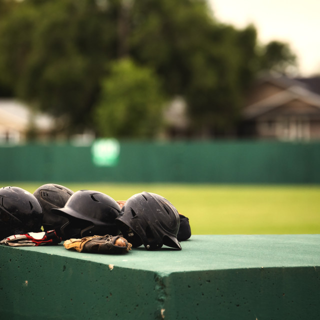 """""""Closeup of four black baseball helmets and a glove on top of the dugout with a blurred baseball diamond in the background in summer"""" stock image"""