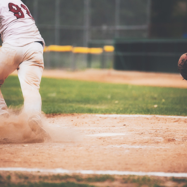 """""""The bottom half of a male baseball player with a cloud of red dust around his feet as he starts running"""" stock image"""