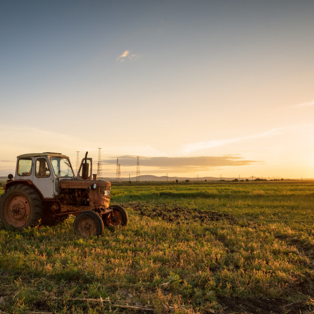 """""""Red tractor on golden sunset sky."""" stock image"""