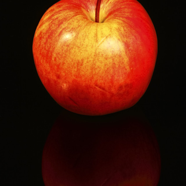 """Red eating apple isolated on black glass with a reflection"" stock image"