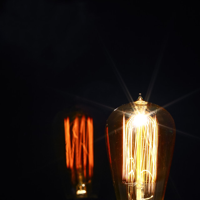 """Clear glass electric lightbulb dimmed to enable it's tungsten filament to be seen with reflection"" stock image"