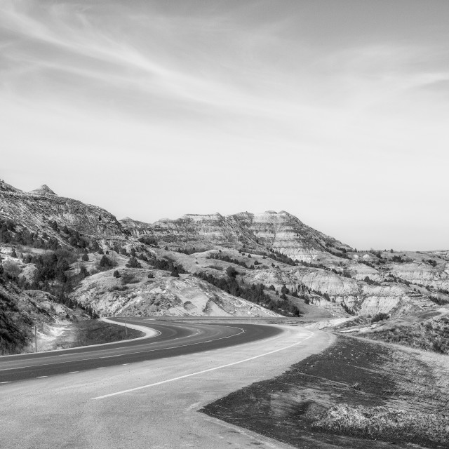 """""""A highway winding down into the badlands in a springtime South Dakota landscape"""" stock image"""