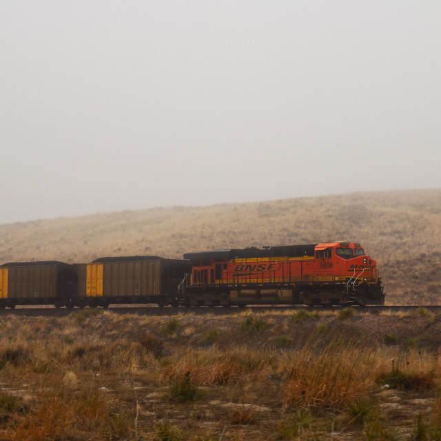 """""""A orange trainengine with attached rail cars loaded with coal moving through the fog along a hillside in a wet sprintime Nebraska landscape"""" stock image"""