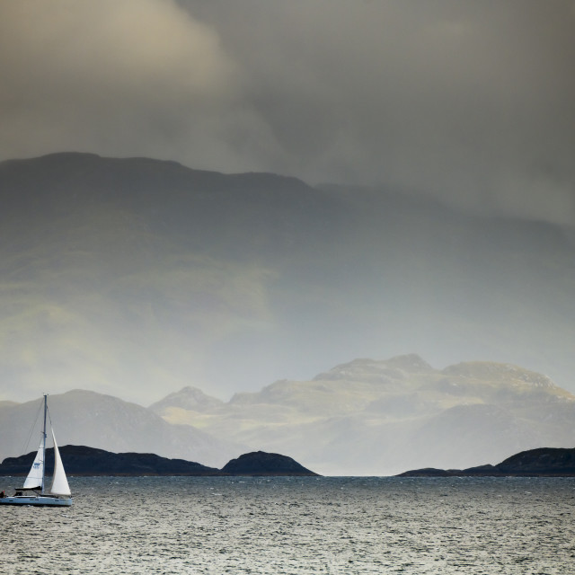 """Yacht sailing along a stormy coast"" stock image"