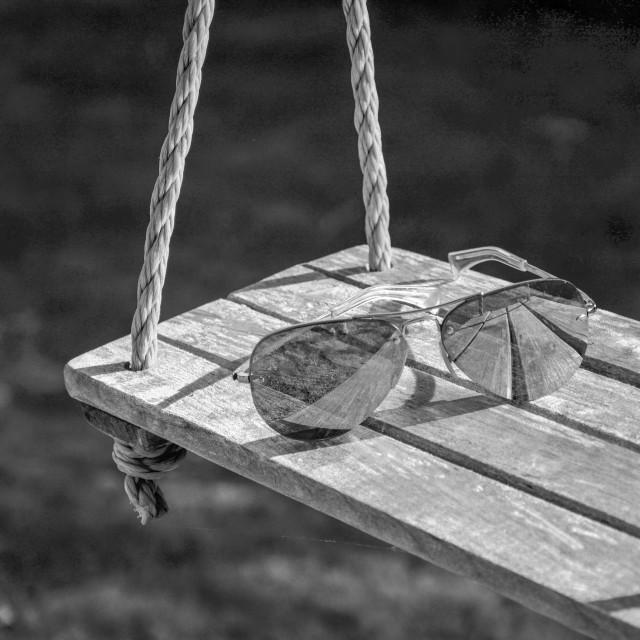 """Sunglasses on a swing."" stock image"