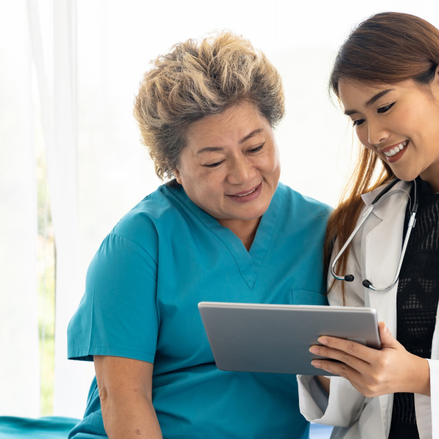 """""""Doctor using tablet with old patient"""" stock image"""