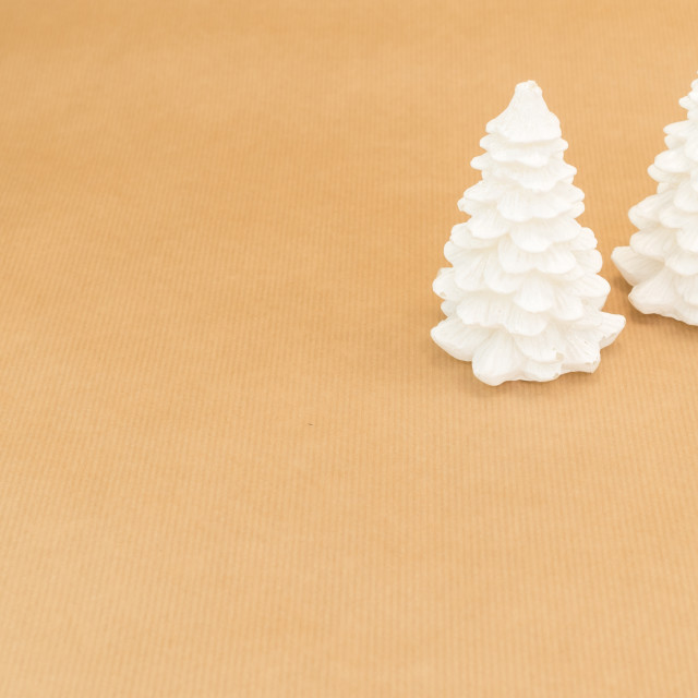 """two white christmas trees decor on a brown paper surface"" stock image"