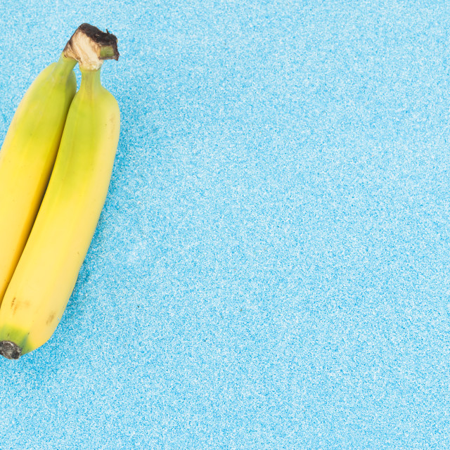 """bananas on a turquoise sand backdrop"" stock image"