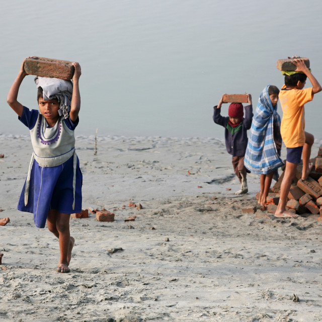 """Child workers carry bricks carrying it on his head in Sonakhali, West Bengal, India"" stock image"