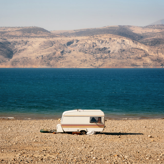 """Caravan on shore of lake among desert and mountains, Uzbekistan"" stock image"