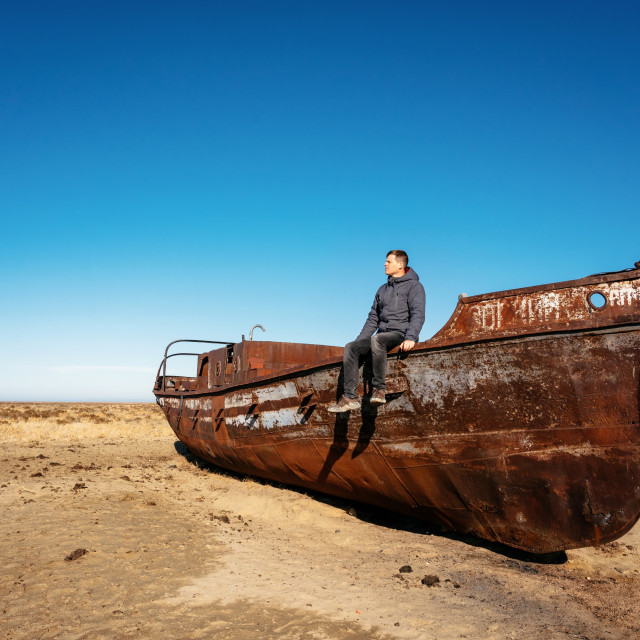 """Man sits on boat in desert in Aral sea, Kazakhstan"" stock image"