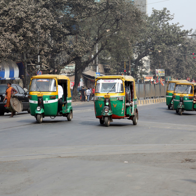 """Auto rickshaw three-weeler tuk-tuk taxi drives down the street in Kolkata"" stock image"