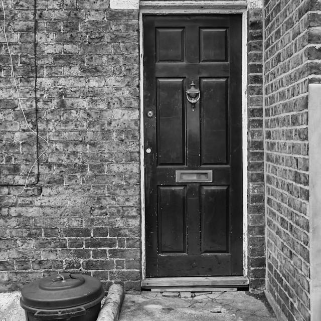"""Trash Bin by an Old Door"" stock image"