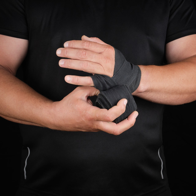 """athlete stand in black clothes and wrap his hands in textile ela"" stock image"