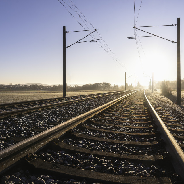 """Railroad tracks and frosty landscape. Rail tracks at sunrise"" stock image"