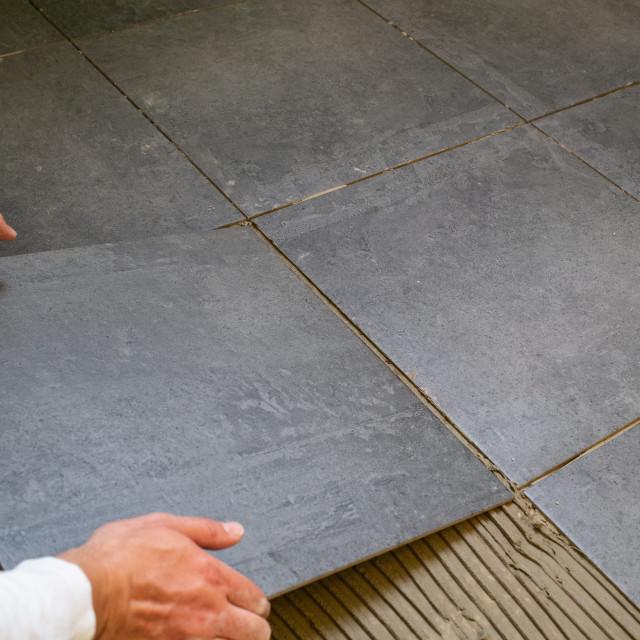 """""""Tiler installing ceramic tiles on a floor"""" stock image"""