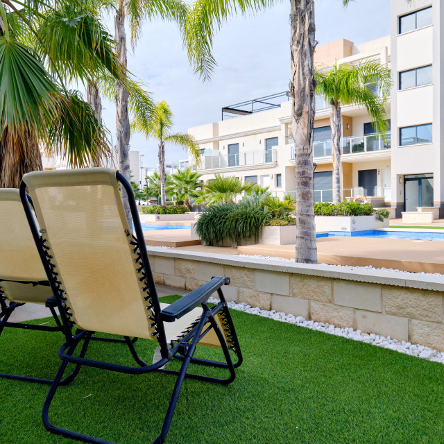 """""""Two empty lounge chairs on artificial lawn grass inside of perso"""" stock image"""