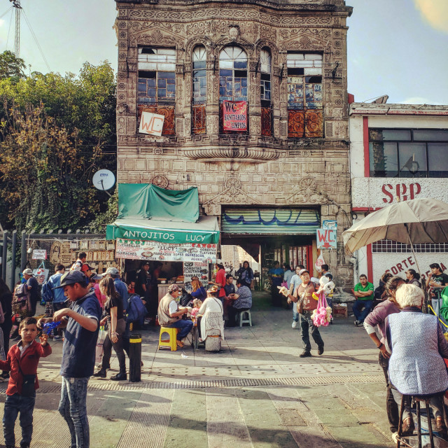 """""""People go about their daily lives in front of a crooked building in Mexico City, Mexico"""" stock image"""