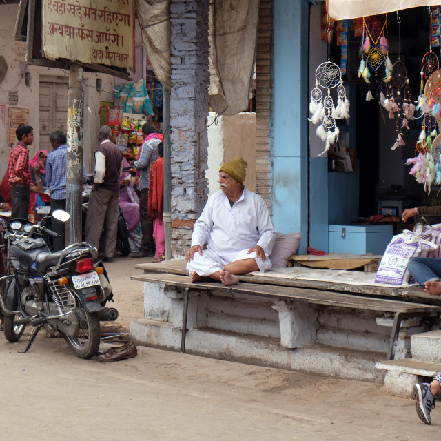 """The owner sits in front of his grocery store in Pushkar, Rajasthan, India"" stock image"