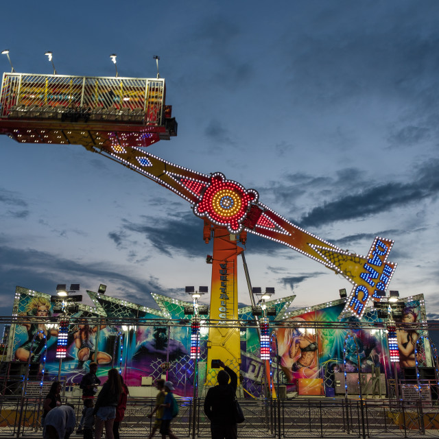 """""""Carousel with many lights turns fast in front of steady spectators"""" stock image"""