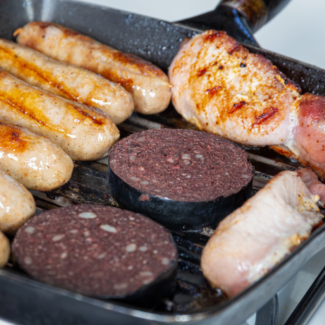 """Sausages, bacon and black pudding cooking in a griddle pan"" stock image"