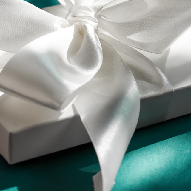 """Luxury holiday white gift box with silk ribbon and bow on emerald green..."" stock image"