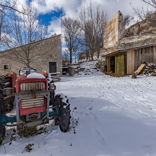 """""""Rural mountain scene of an old tractor parked in a snowy courtya"""" stock image"""