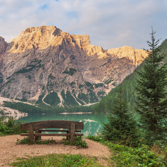 """""""Wooden bench overlooking the Braies lake and the rocky wall"""" stock image"""