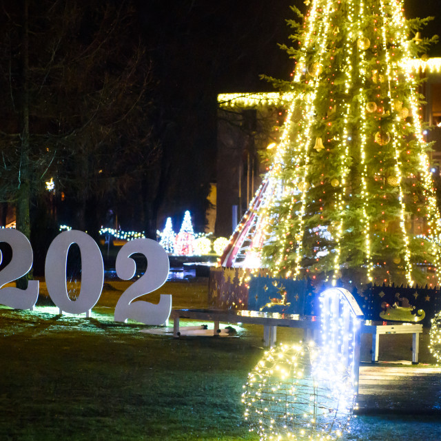 """""""Year 2020 sign with fallen 0 sign in front of Christmas tree.Gulbene, Latvia."""" stock image"""