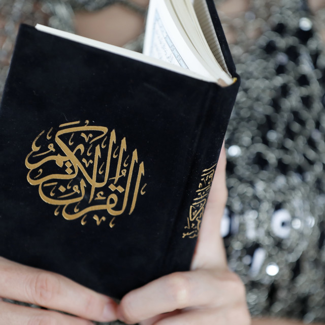 """""""Woman reading the Noble Quran. Close-up."""" stock image"""
