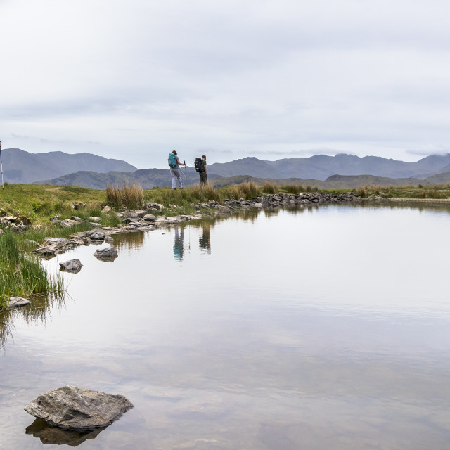 """Walkers Walking Alongside Alcock Tarn, Grasmere, Lake District,"" stock image"