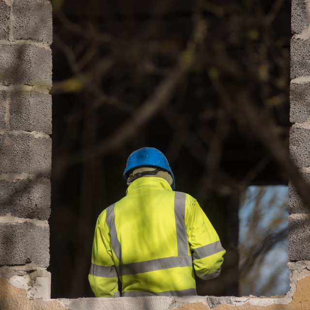 """""""Worker with blue plastic helmet and yellow reflecting vest at building yard. Riga, Latvia."""" stock image"""