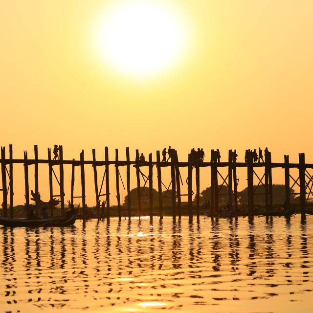 """silhouette of people and monks walking on ubien bridge"" stock image"