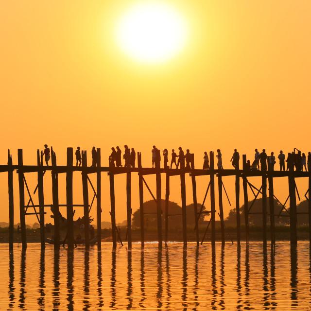 """silhouette of people walking and boat at ubien bridge"" stock image"