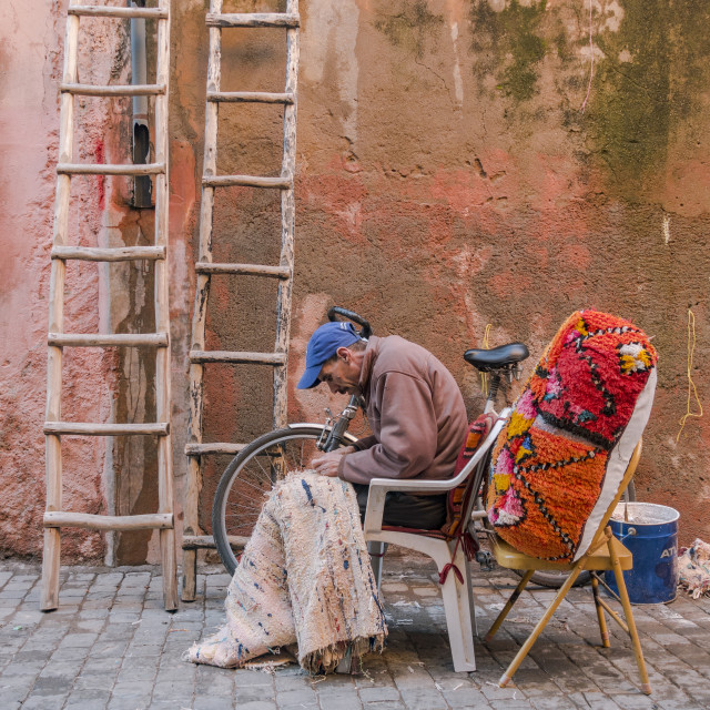 """""""Man working on a Moroccan rug"""" stock image"""