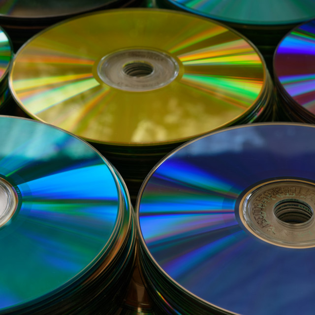 """""""Gold, purple, blue and teal DVDs in stacks"""" stock image"""