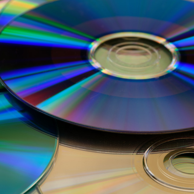 """""""A purple, shiny cd on top of a desk and other cds"""" stock image"""
