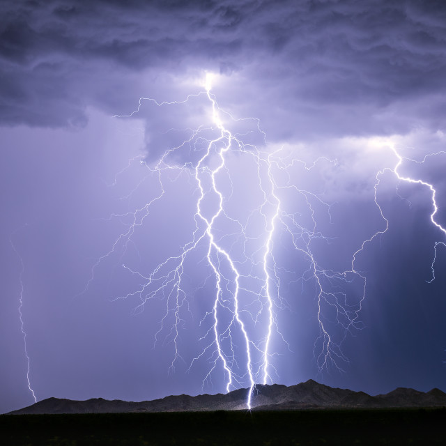 """Lightning bolts strike a mountain during a storm"" stock image"