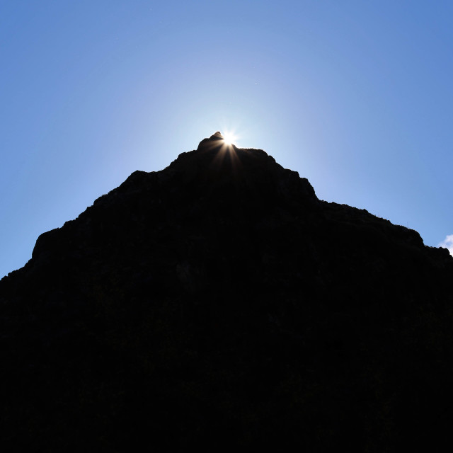 """Sunlight Shining from behind a Volcanic Hill in Iceland"" stock image"