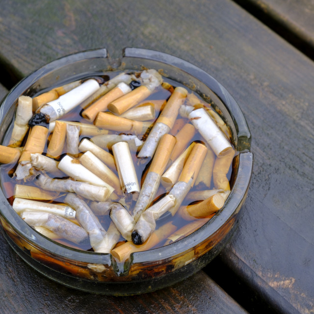"""""""Water logged outdoor ash tray full of cigarette butts on a table after rain"""" stock image"""