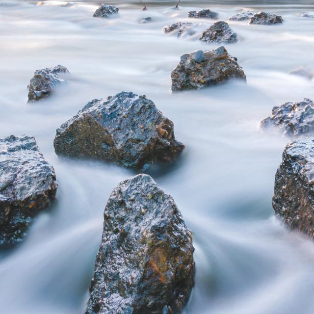 """Soft flowing water crashing against rocks"" stock image"