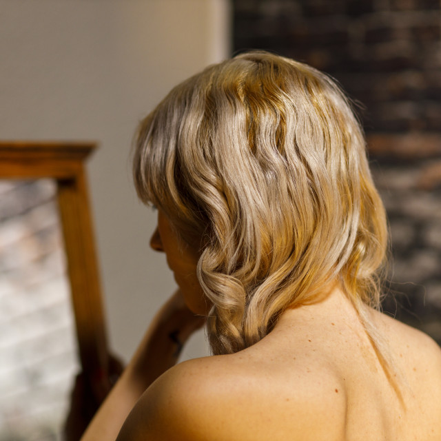 """""""Young Blonde Woman Looks Into a Mirror"""" stock image"""