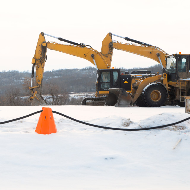 """""""Orange industrial pylons roped off in front of a loader and excavator in a valley in a winter landscape"""" stock image"""