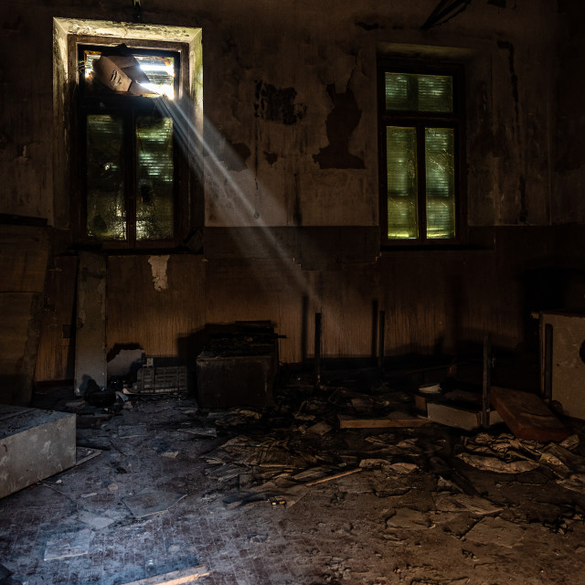 """""""Rays of light filter through the window of a room of an abandone"""" stock image"""
