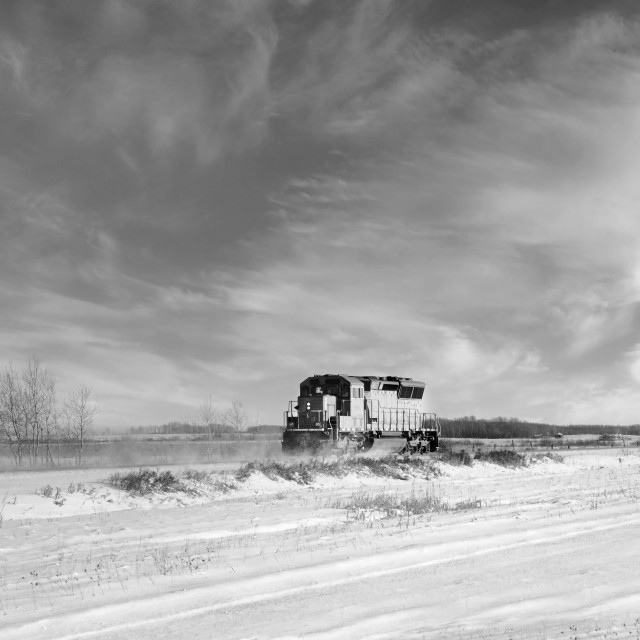 """""""A red locomotive engine travelling down a railway track in a forested prairie winter landscape"""" stock image"""