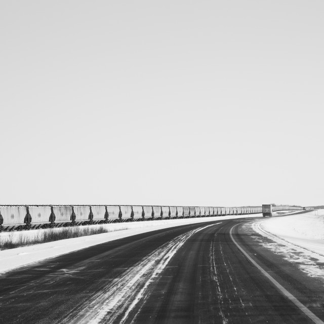 """""""A very long row of agricultural dry product railway cars beside a curving highway in a black and white Canadian prairie winter landscape"""" stock image"""