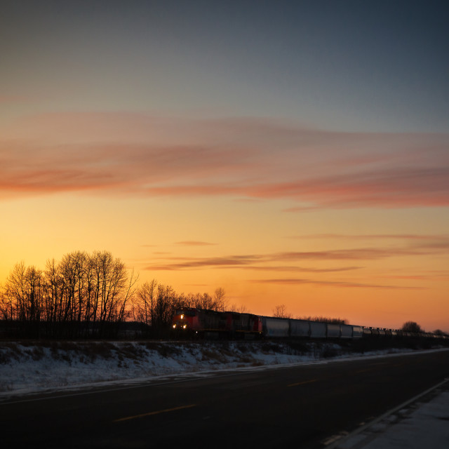 """""""An industrial freight train illuminated by headlights travelling at sunset along a deserted highway in a prairie winter landscape"""" stock image"""
