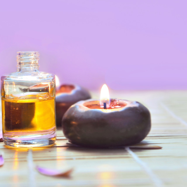 """oil bottles with candles light on a table on pink background"" stock image"