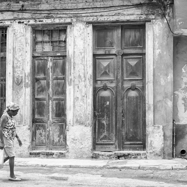"""A woman walks past a characterful building in Havana, Cuba"" stock image"